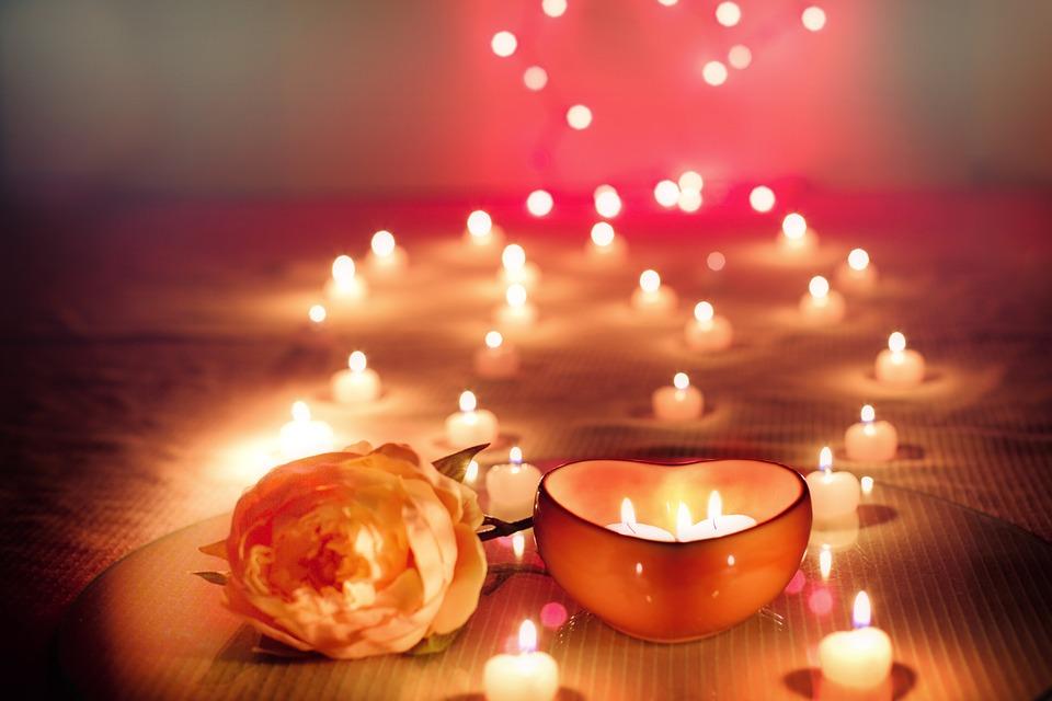 Bougies romantiques en forme de coeur avec une rose