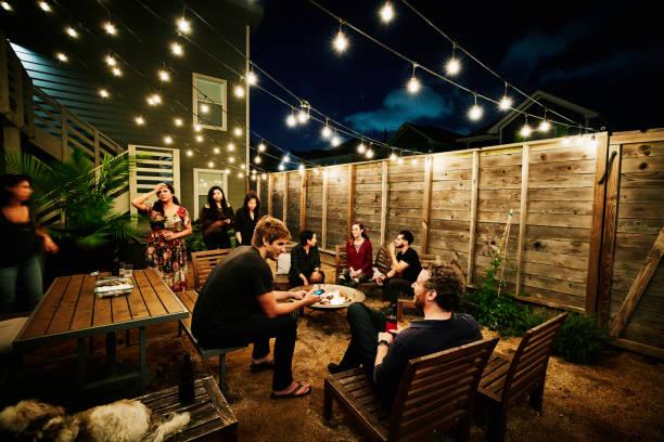 Salon de jardin avec guirlandes lumineuses, chaises et tables basses