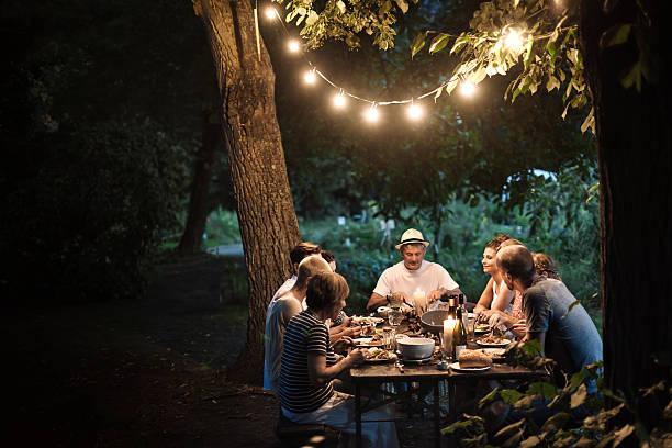 Famille qui dîne dans le salon de jardin, éclairée par une guirlande lumineuse accrochée à un arbre